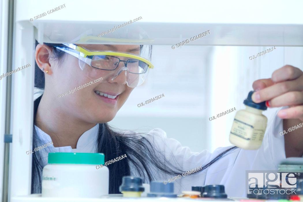 Imagen: Female scientist selecting chemical from shelf in laboratory.