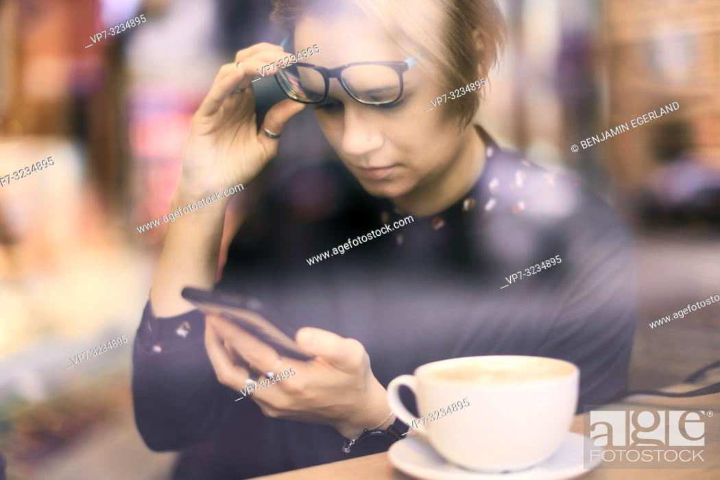 Stock Photo: woman behind glass window touching glasses, using smartphone next to coffee cup in café in Munich, Germany.