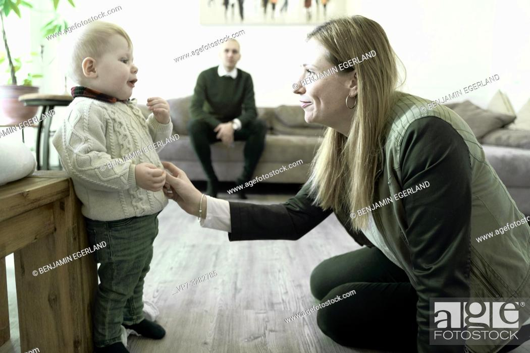 Photo de stock: mother with baby toddler child in living room, looking at each other, blurred father watching in background, in Cottbus, Brandenburg, Germany.
