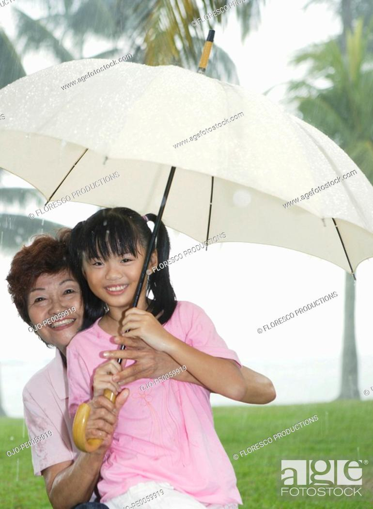 Stock Photo: Woman and young girl outdoors in park by lake with umbrella.