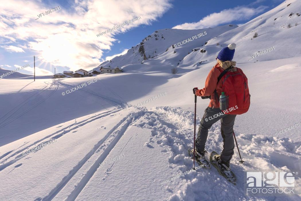 Imagen: Young girl walks with snowshoes in the fresh snow at sunset. . Grevasalvas, Engadin Valley, Graubünden, Switzerland, Europe.