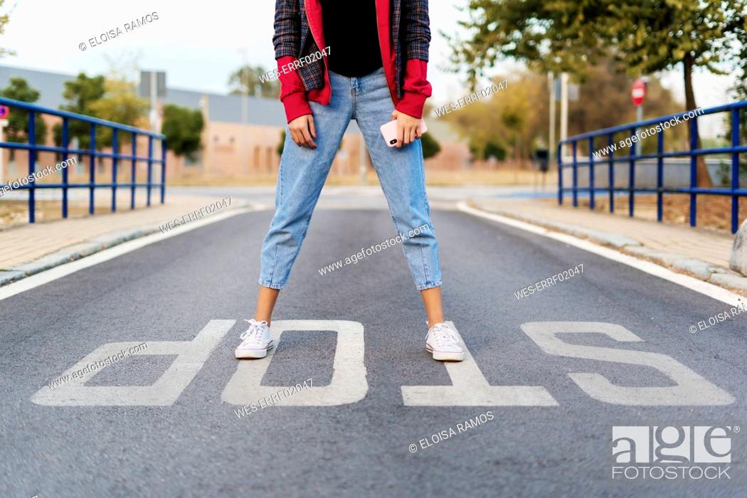 Stock Photo: Crop view of young woman with mobile phone standing on the word 'stop' on the street.