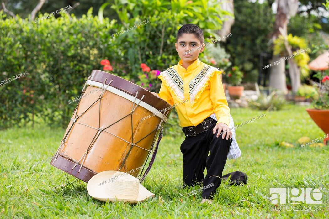 Imagen: Young boy in Farmer's clothing hat and drum posing for camera in a photo shoot.