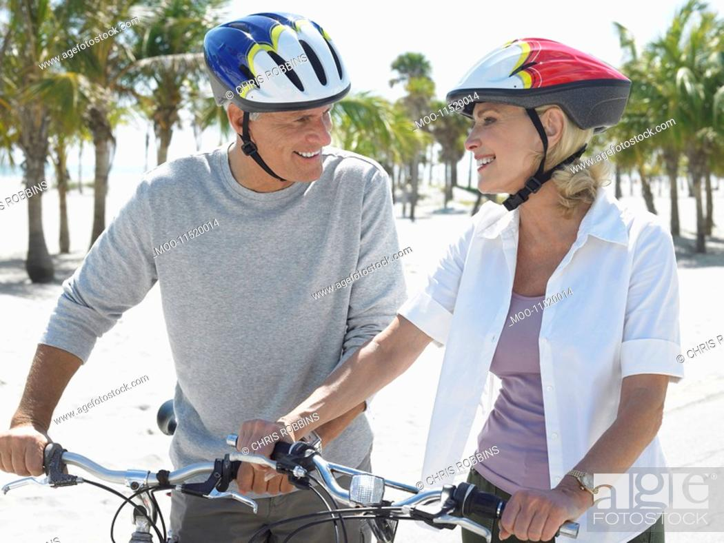 Stock Photo: Senior couple on bicycles on tropical beach.