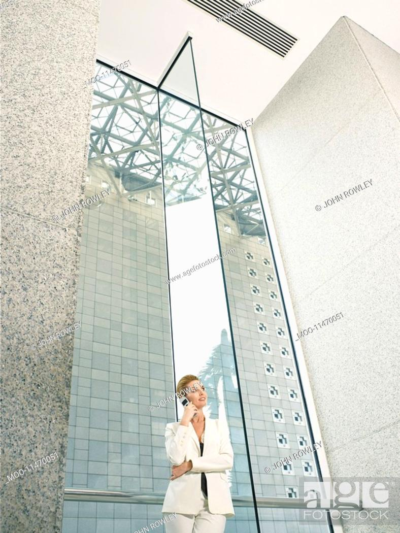 Stock Photo: Businesswoman using mobile phone in office building low angle view.