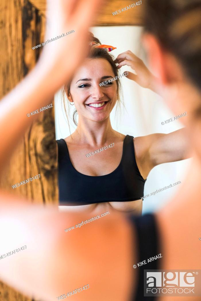 Stock Photo: Mirror image of smiling young woman wearing bra.