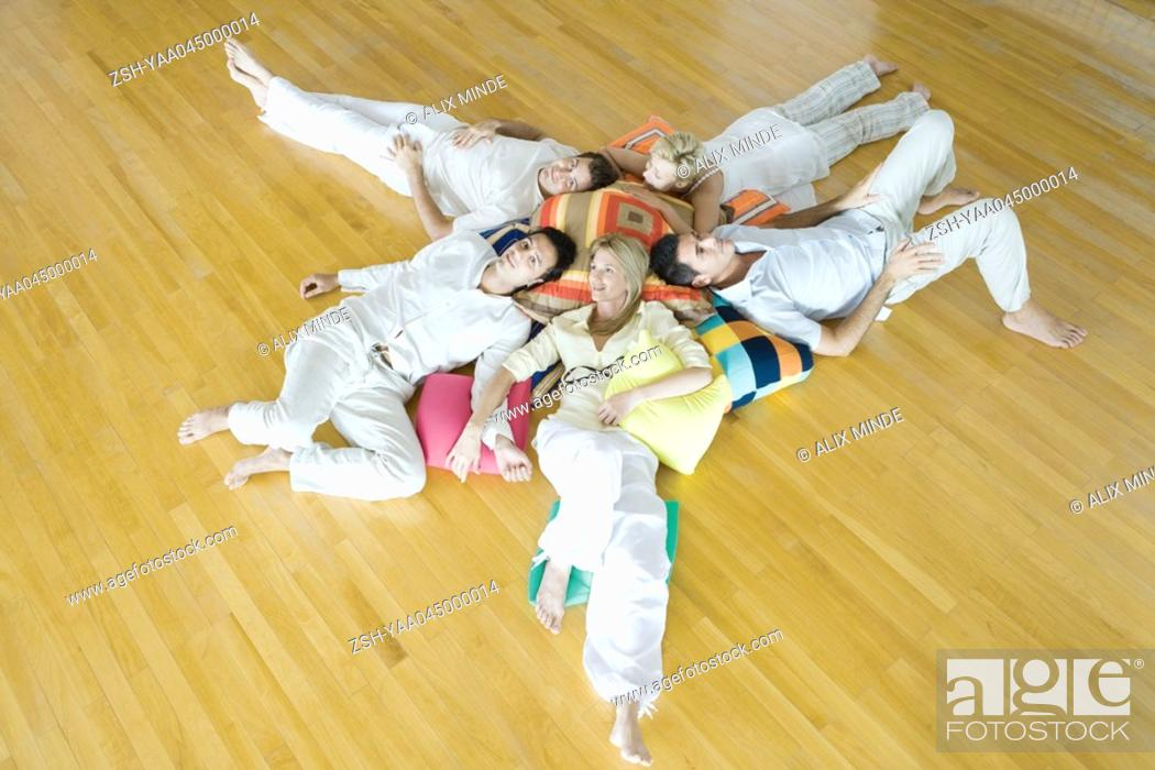 Stock Photo: Group therapy, adults lying on ground with heads together on cushions.