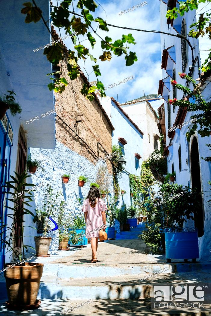 Stock Photo: Morocco, Chefchaouen, back view of woman walking alley upstairs.