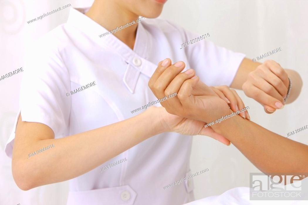 Stock Photo: Nurse taking pulse for the patient.