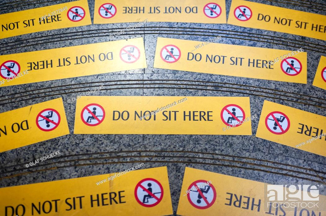 Stock Photo: Singapore, Republic of Singapore, Asia - Yellow prohibition signs are seen on steps at a MRT station (subway station) that read Do Not Sit Here.