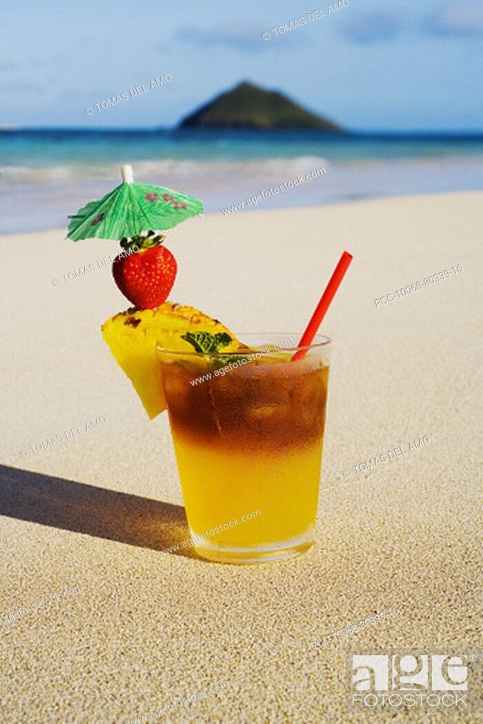 Stock Photo: A mai tai garnished with pinapple and a strawberry, sitting in the sand on the beach.