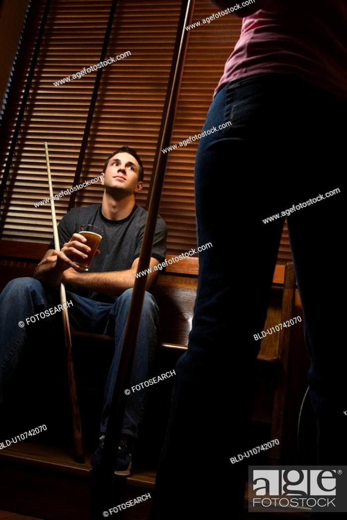 Stock Photo: Young man with billiards cue looking at woman standing before him.