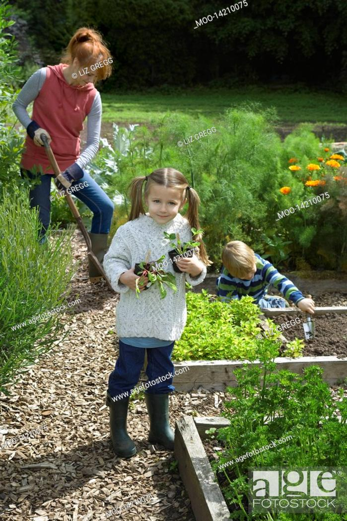 Stock Photo: Mother gardening with two children 5-6 in countryside.