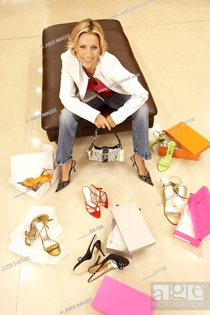 Stock Photo: Blonde woman trying on different pairs of high heels in shoe shop, portrait, elevated view.