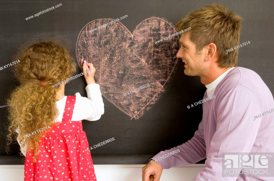 Stock Photo: Girl drawing on a blackboard with her father watching her.