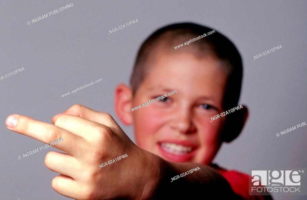 Stock Photo: Young boy making an obscene gesture.