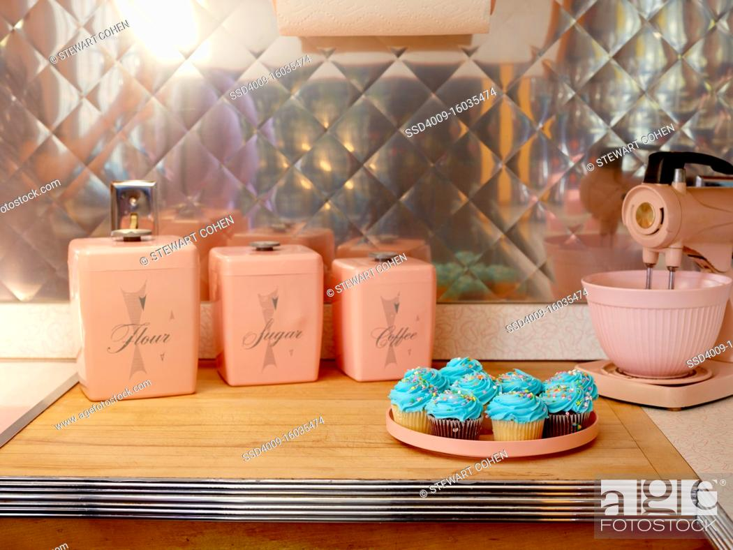 Stock Photo: Mid century kitchen with pink appliances and blue cupcakes.