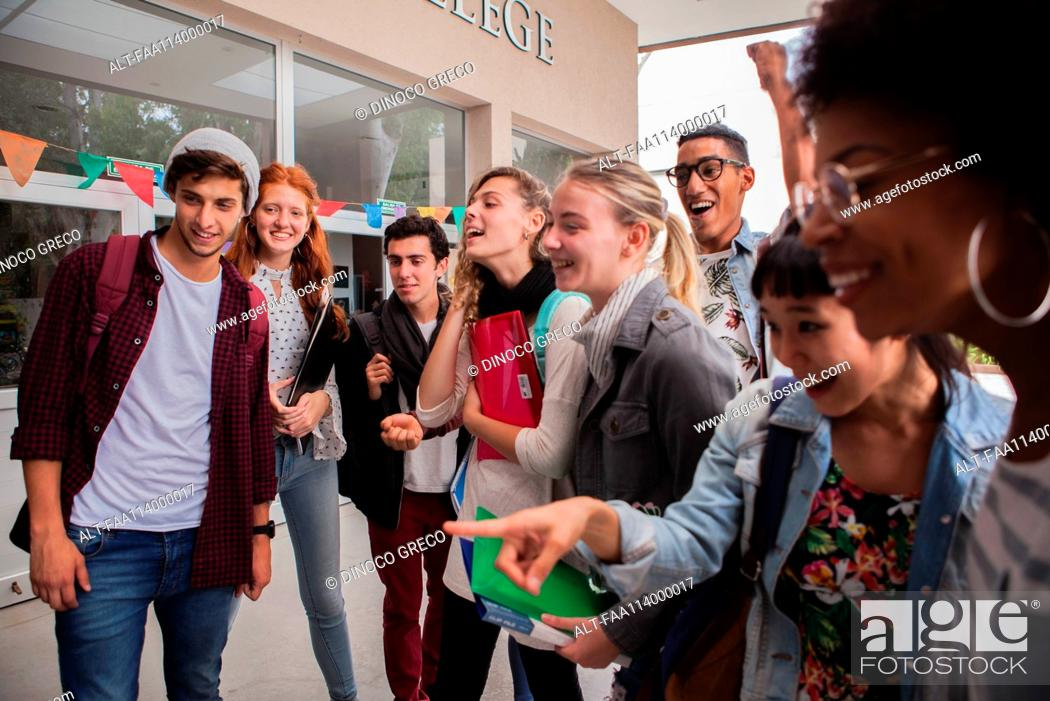 Stock Photo: College students gathered together on campus, looking excited.