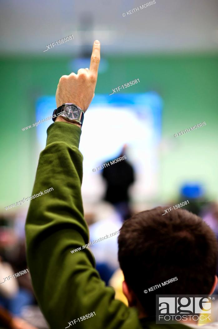 Stock Photo: Rear view of a young man holding his hand up to ask a question in a meeting, UK.
