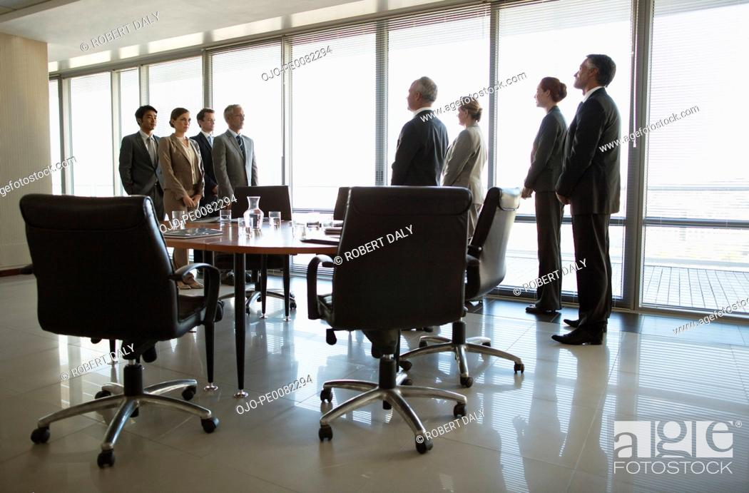 Stock Photo: Separate groups of business people facing off in conference room.