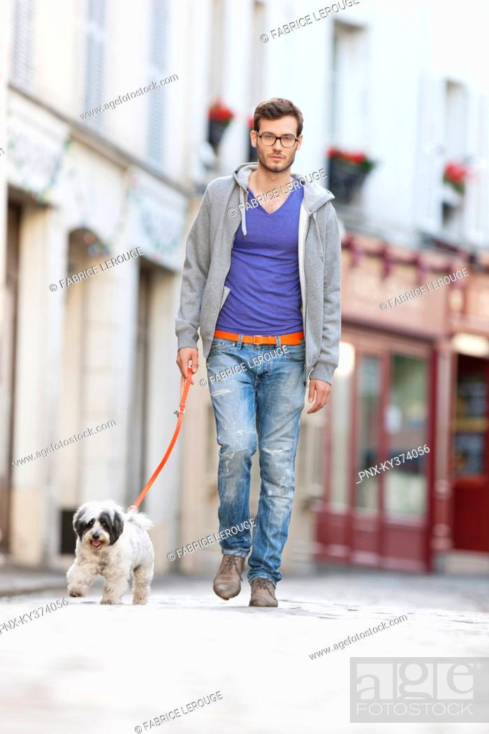 Stock Photo: Man holding a dog on leash walking on the street, Paris, Ile-de-France, France.