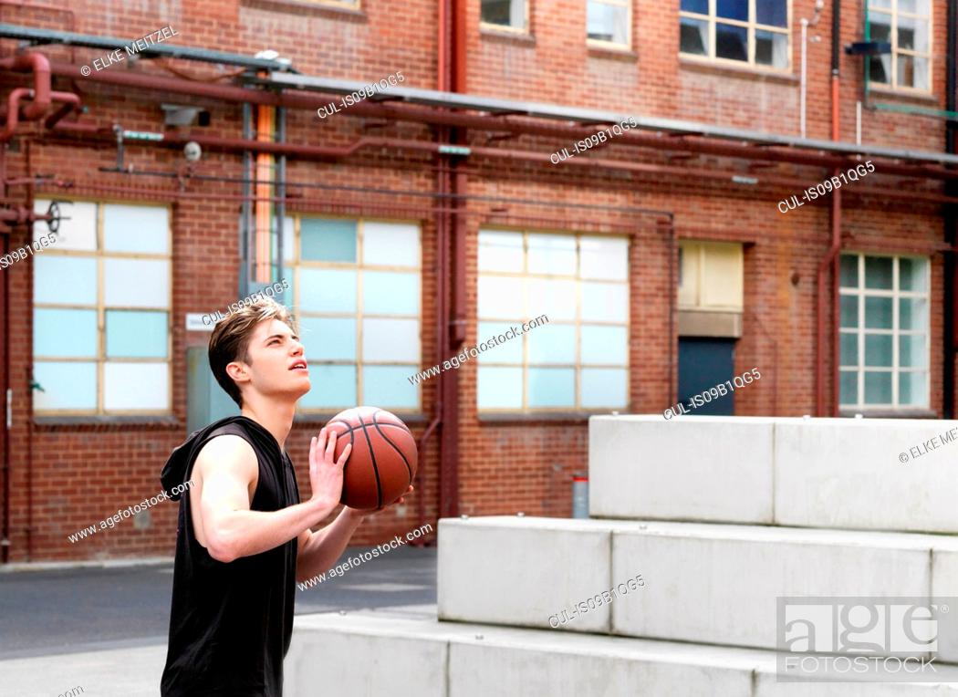 Stock Photo: Young man playing basketball in outdoor court.