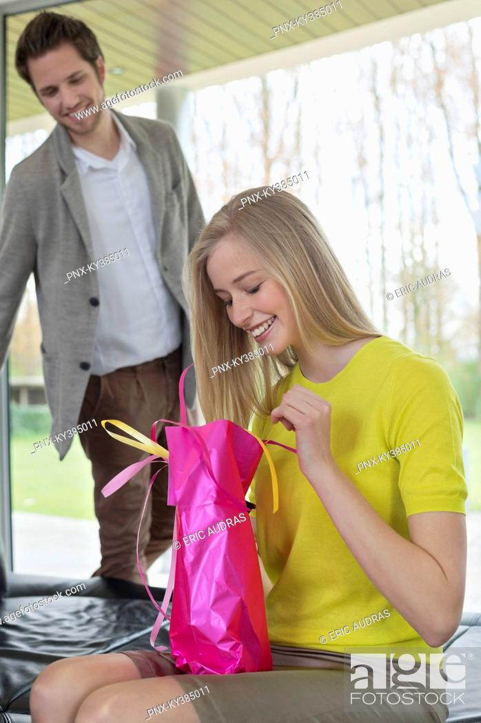 Stock Photo: Happy woman opening a present given by her boyfriend.