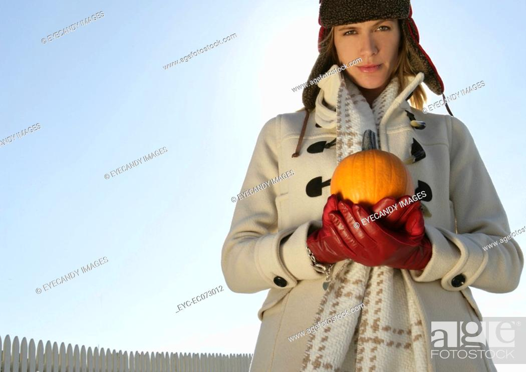 Stock Photo: Young woman holding pumpkin.