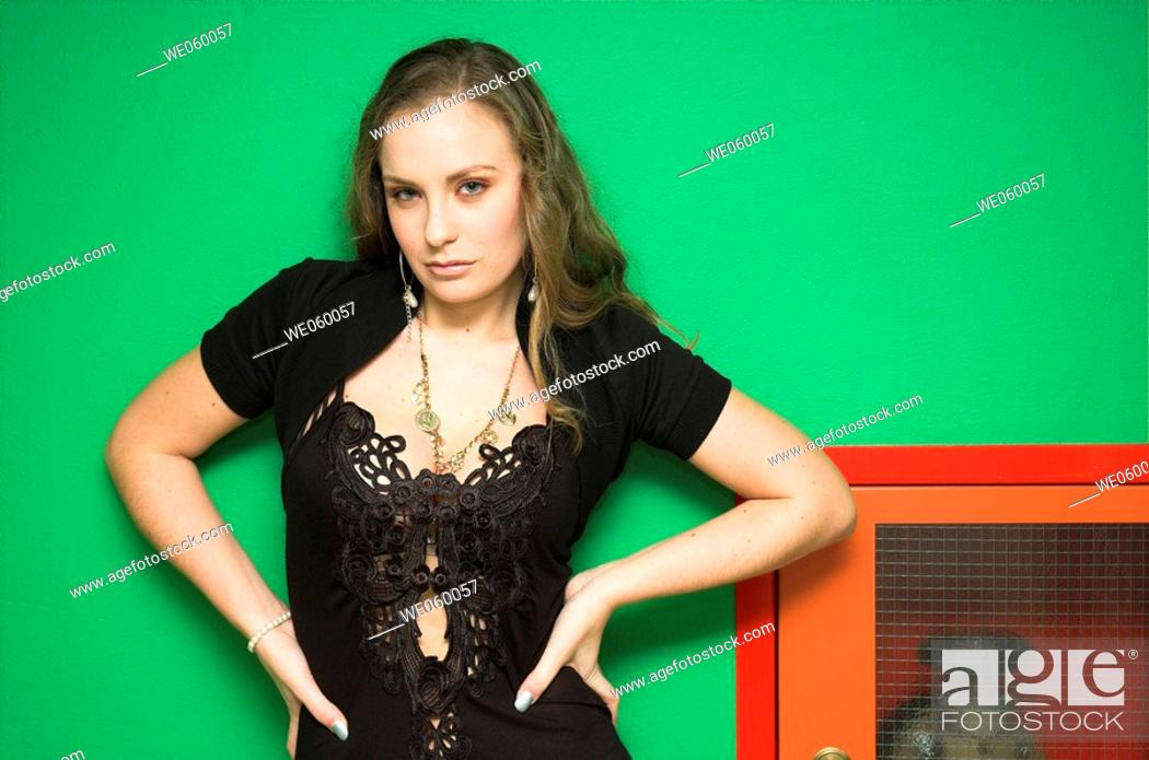 Stock Photo: Young female fashion model posing against a green wall and fire hydrant.