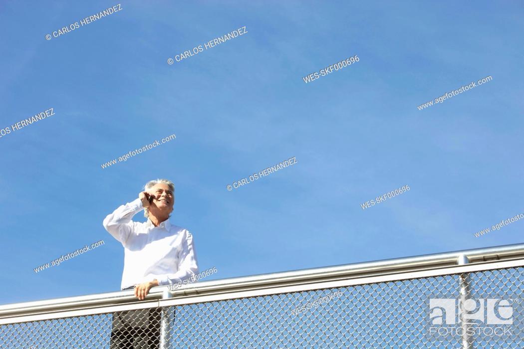 Imagen: Germany, Bavaria, Munich, Businessman talking on phone, smiling.