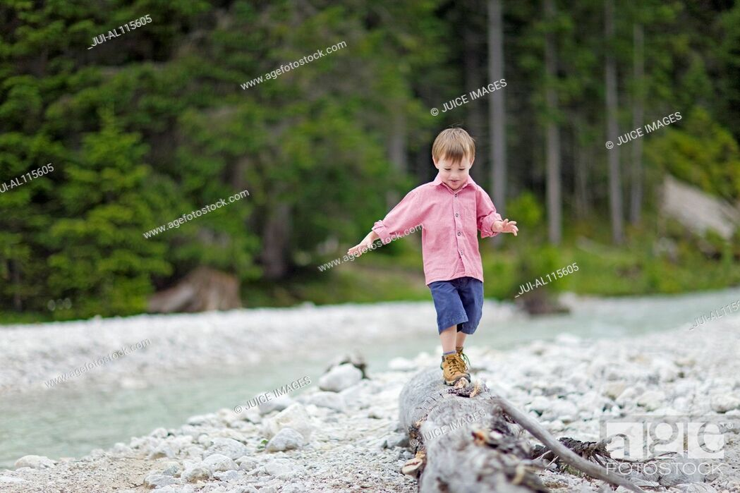 Stock Photo: Young boy balancing on log next to stream.
