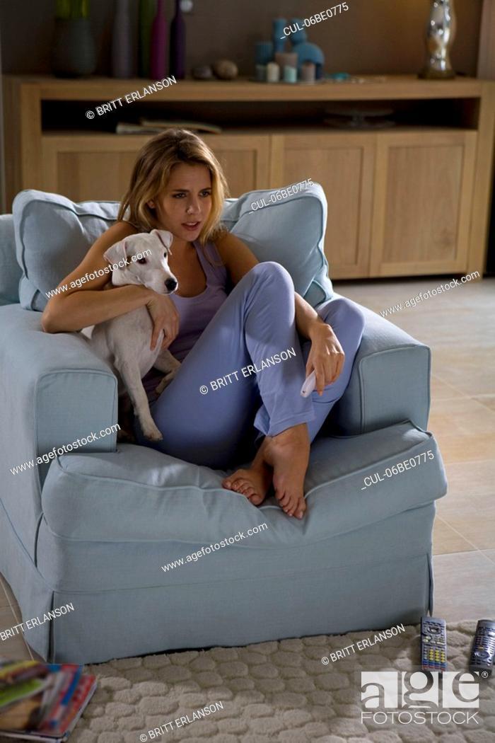 Stock Photo: Woman and dog, sitting, watching tv.