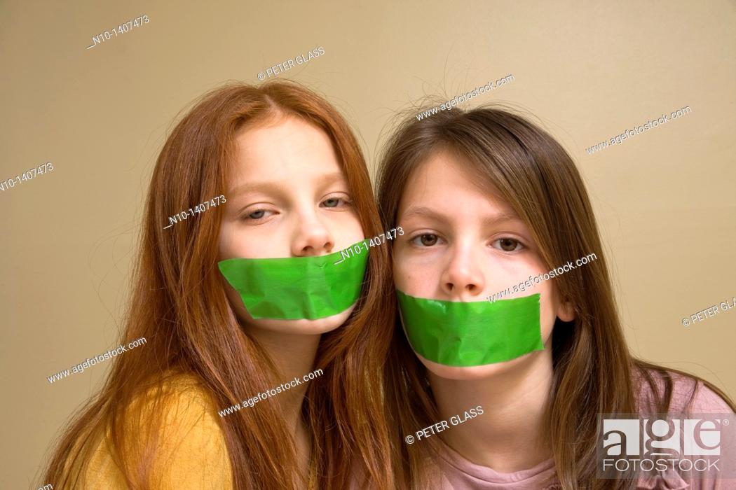 Stock Photo: Preteen girls with green tape on their mouths.