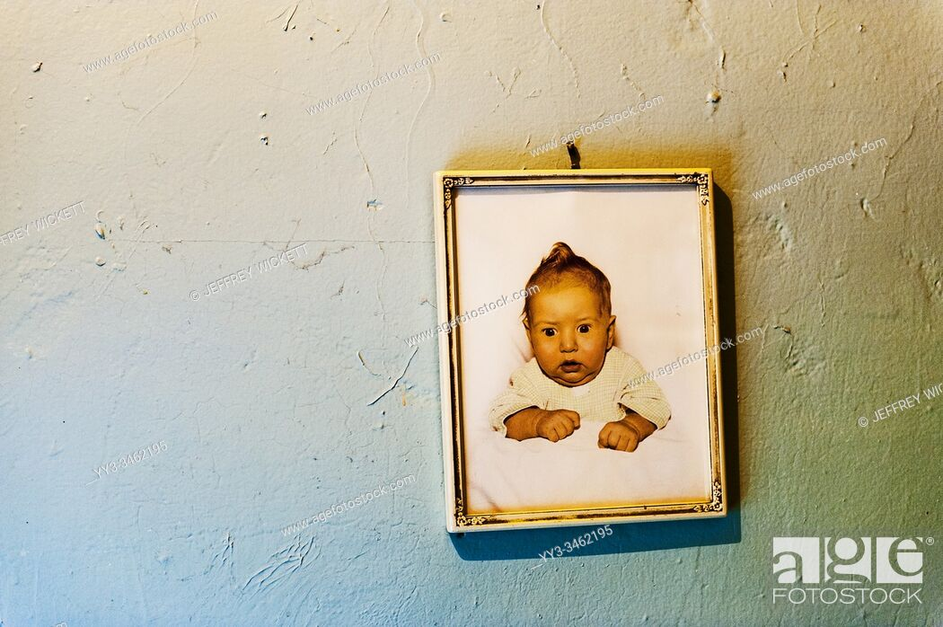 Stock Photo: Framed baby picture from the 1950s hanging on the wall.