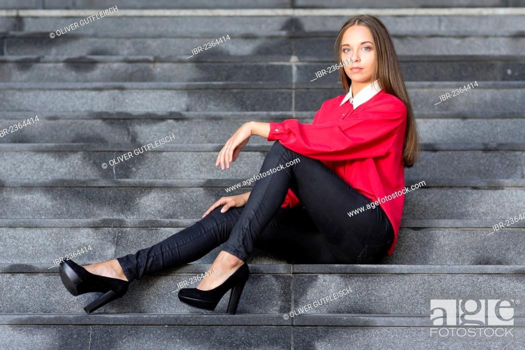 d8bc6242a6693f Stock Photo - Young woman wearing a red top, black jeans and high heels  posing while sitting on stairs
