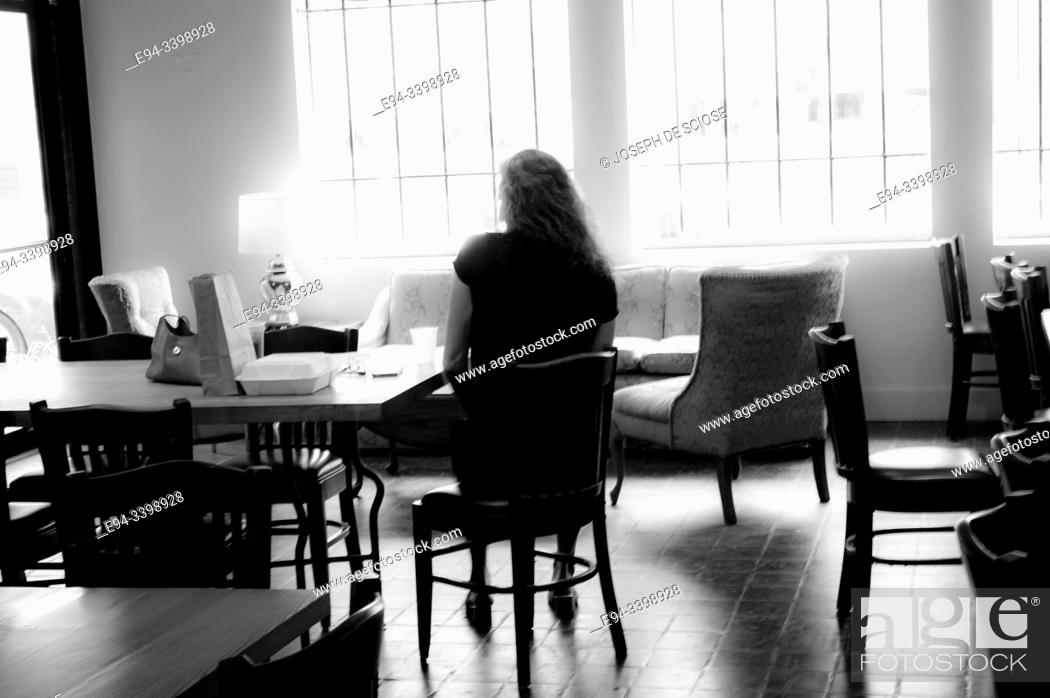 Photo de stock: A single woman sitting by herself in a restaurant.