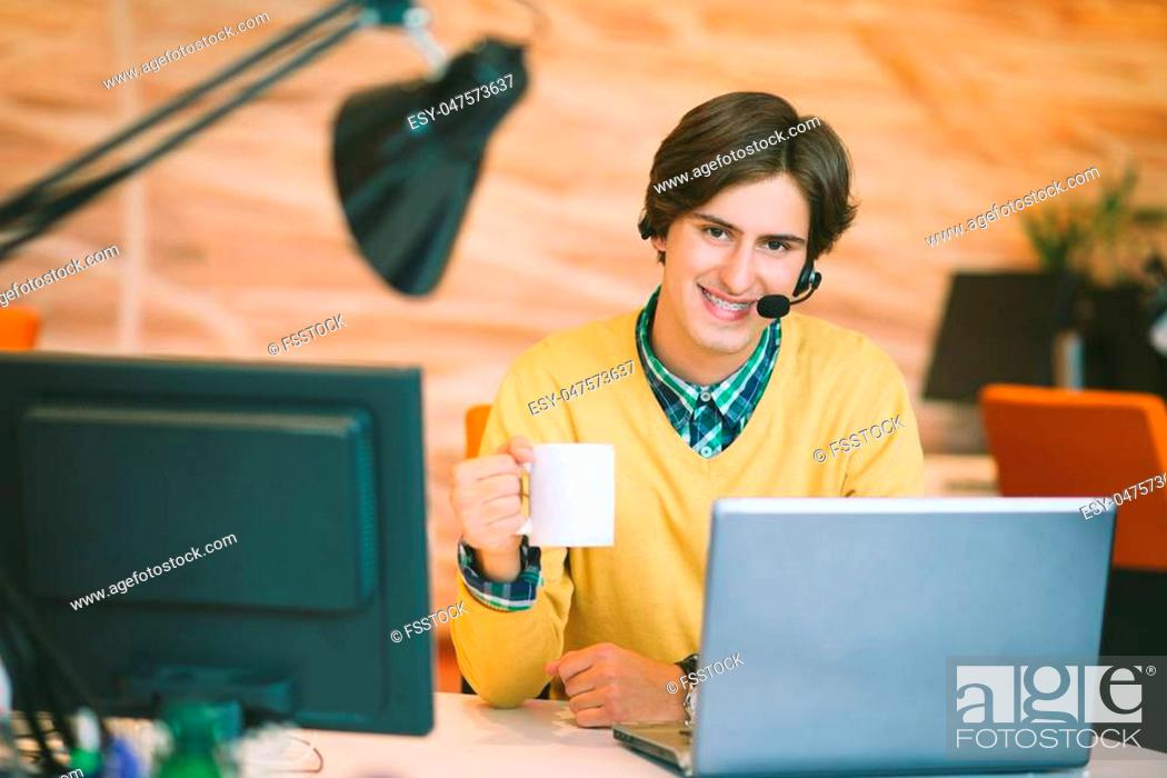 Stock Photo: Portrait of young man sitting at his desk in the office.