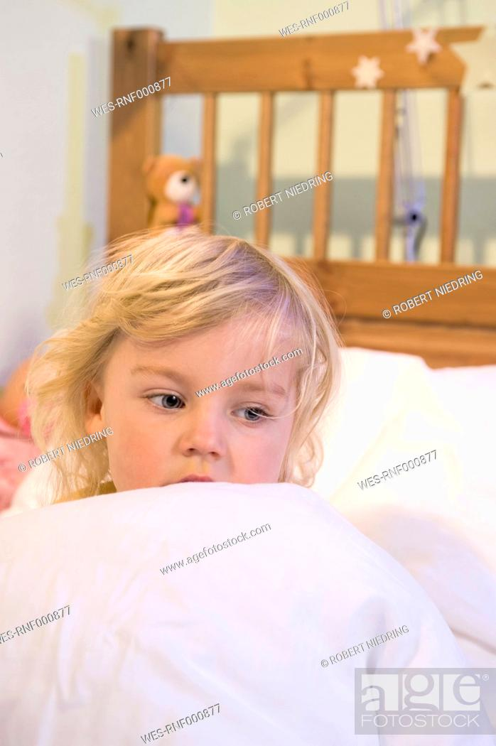 Stock Photo: Girl covered with blanket on bed, close up.