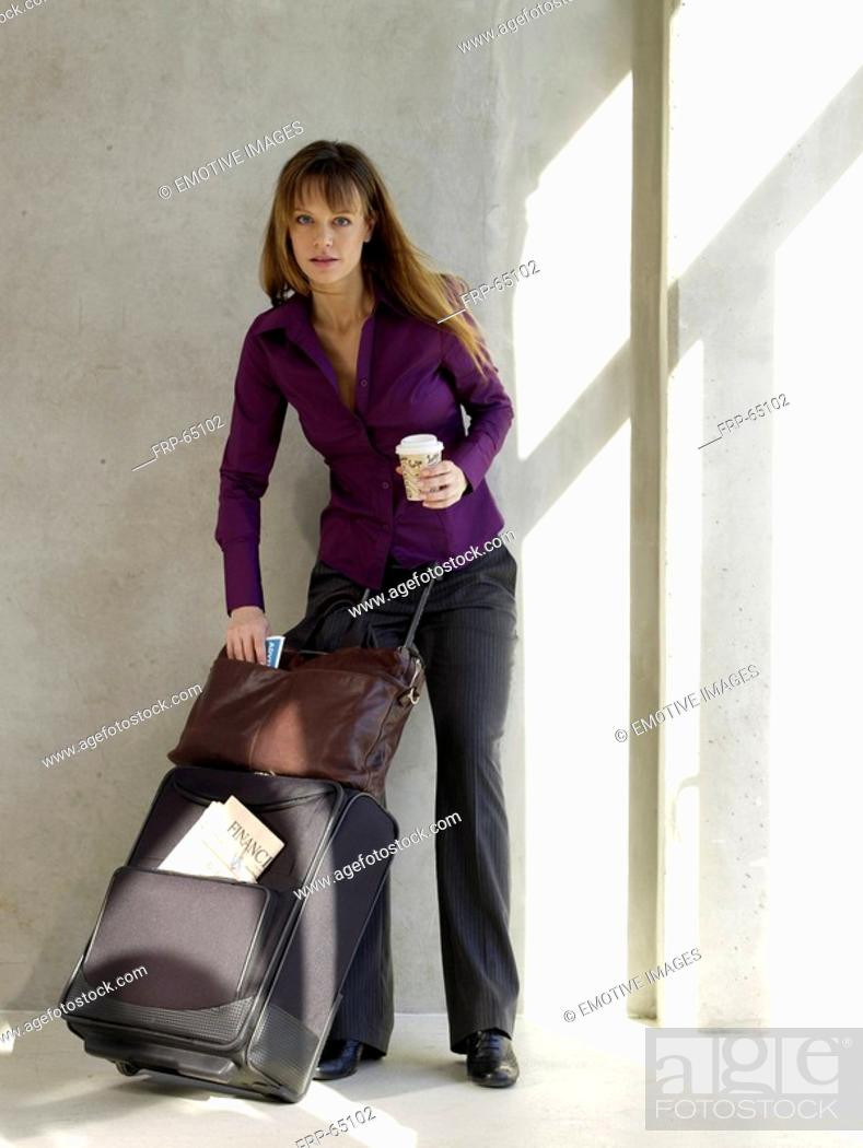 Stock Photo: Business woman with baggage holding a cup of coffee.