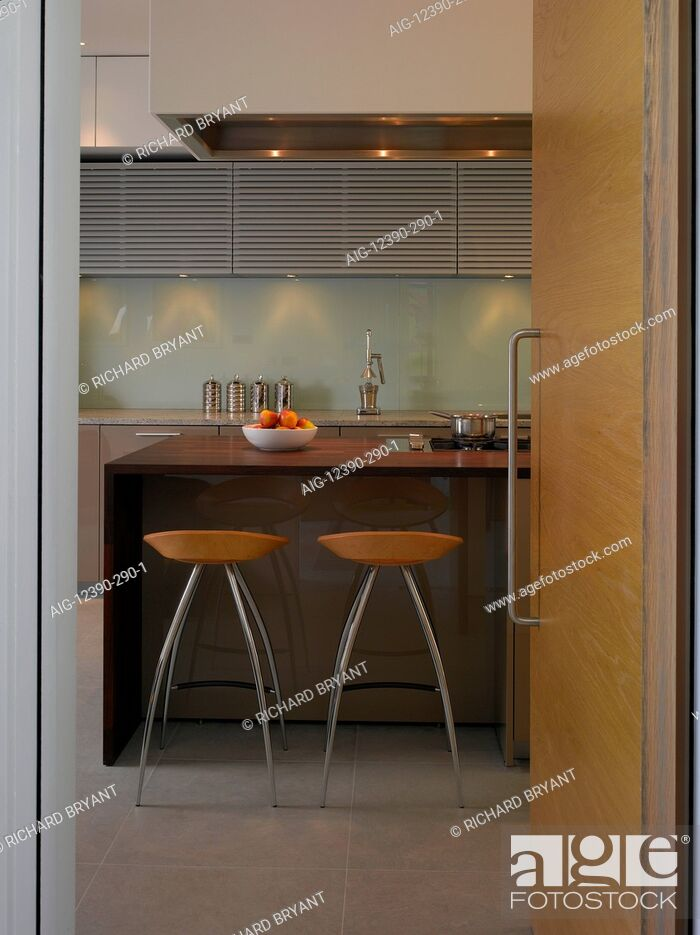Stock Photo: Pond and Park House, Dulwich, London. View through open pale wood modern door to kitchen with bar stools.