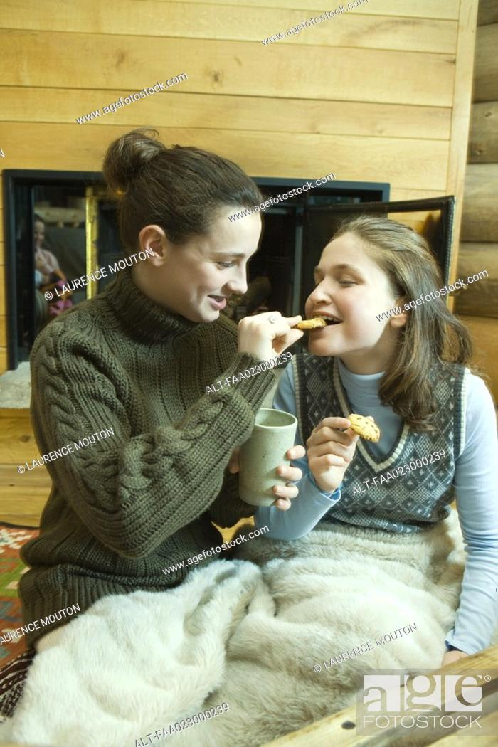 Stock Photo: Teen girls having snack by fire place.