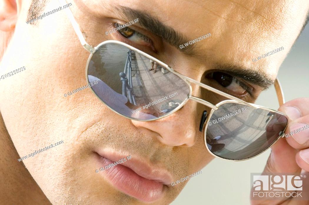 Stock Photo: Close-up of a mid adult man peeking over his sunglasses.