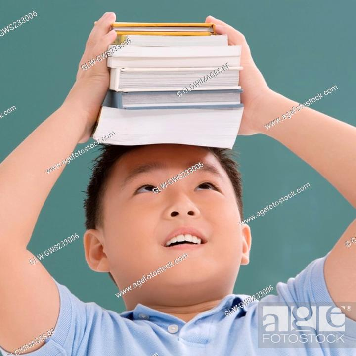 Stock Photo: Close-up of a schoolboy holding books on his head.