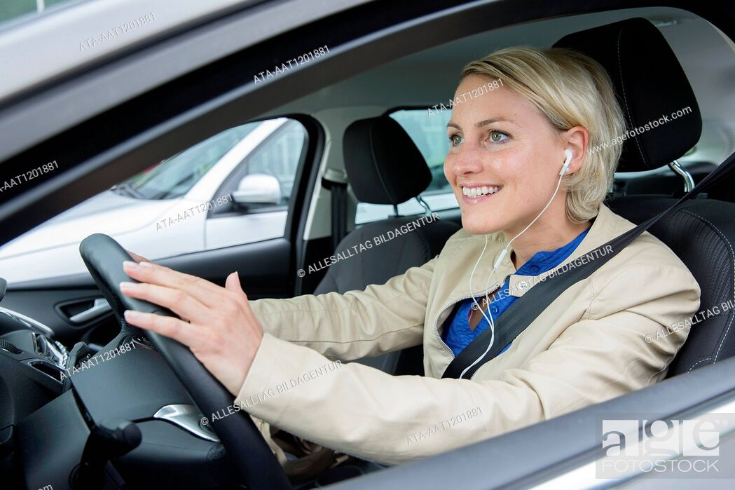 Stock Photo: Female car driver is hearing music.