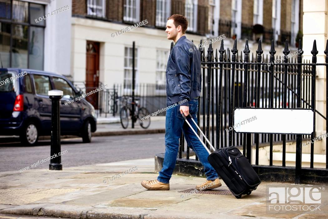 Stock Photo: A young man pulling his suitcase in the street.