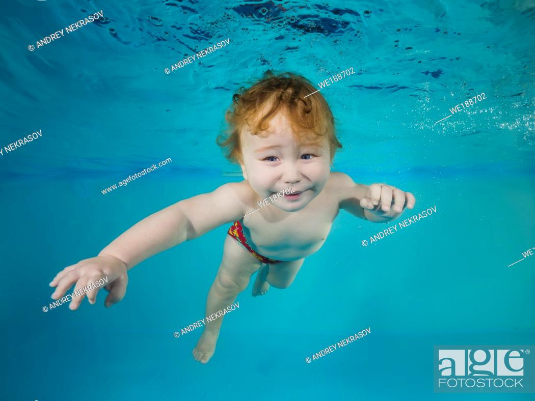 Stock Photo: Funny red-haired boy plays underwater in a swimming pool.