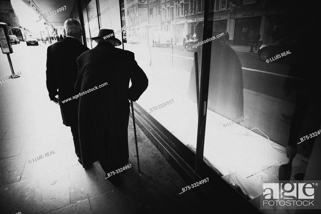 Stock Photo: An old man with a hat and a walking stick in the city. London, UK, Europe.