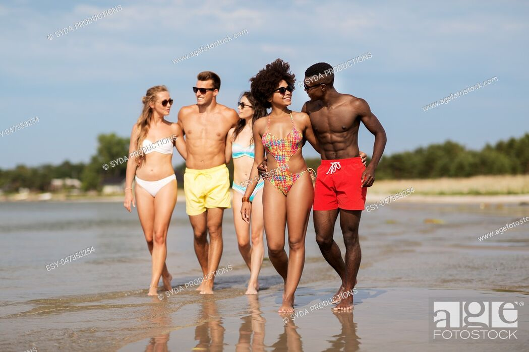 Stock Photo: mixed race couple walking along beach with friends.