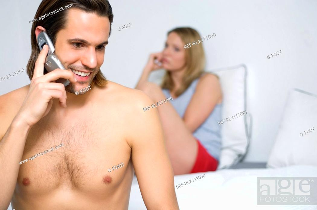 Stock Photo: Couple in bedroom ignoring each other.