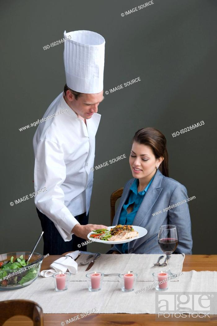 Stock Photo: A chef serving a woman with a meal.